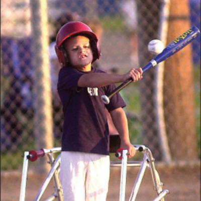 A young boy stands on a baseball field. He is wearing a red helmet, a black shirt, and white baseball pants. He is using a walker mobility device. He is swinging a blue baseball bat at a white baseball.