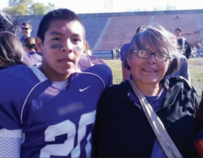 A son and mother stand together on the side of a football field, smiling at the camera. They are both Native American. The son is on the left in a purple football jersey with lines painted under his eyes. The mother is on the right with short gray hair and glasses. She is wearing a purple shirt and a black jacket.