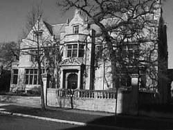 Grayscale image of a large, historic-looking building. It is at least two stories high and has a short, stone fence. The building is made of stone and has many windows.