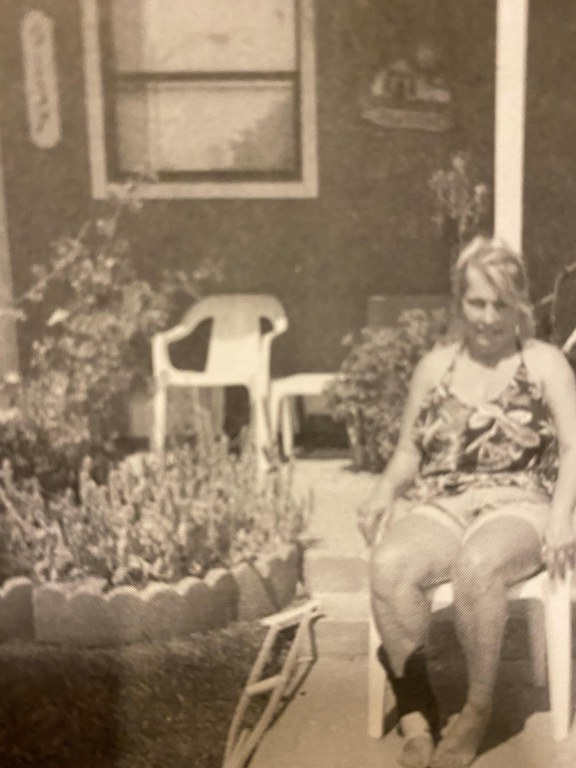 This is a faded color photograph of a woman sitting on a plastic chair outside of a home. There are many flowers. She is wearing a floral tank top and shorts and has her hair pulled back in a bun.