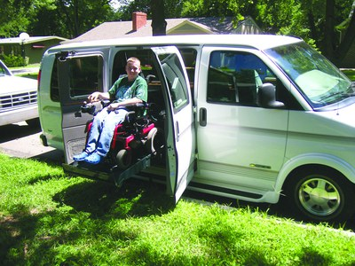 A teenage boy in a power chair on a wheelchair lift into a van smiles at the camera. He is wearing a green t-shirt and jeans. The van is parked on a curb next to a green lawn.