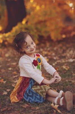 A young female child in a white shirt and multi-colored shirt sits on the grass with her arms in front of her and her legs crossed. She has short brown hair and she is smiling. Behind her is a tree along with many red, yellow, and green leaves.