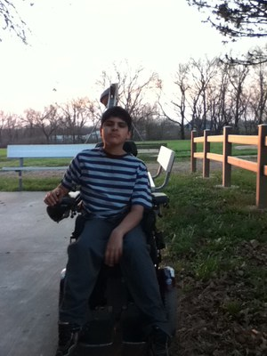 A young man with dark hair in a power chair is in front of grass and a wooden fence. He is wearing a striped shirt and jeans and is looking at the camera.