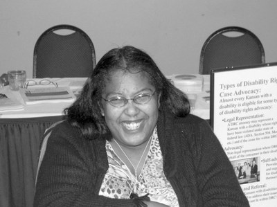 Black and white photo of a woman sitting indoors. She is smiling at the camera. She has dark hair and skin and thin wire glasses. She is wearing a button down shirt and a cardigan.