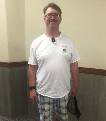 A middle-aged white man with a mustache and glasses stands in front of a wall. He is wearing a white shirt, plaid shorts and a watch. He has a hat in his hand. He is smiling at the camera.