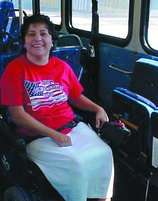 A woman is sitting on a bus seat. She is wearing her seatbelt. She has short brown hair and is smiling at the camera. She is wearing a red shirt with an American flag on it and a long white skirt.