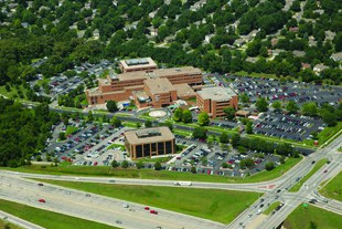 Birdseye view of a hospital facility. It is surrounded immediately by parking lot and then by trees.