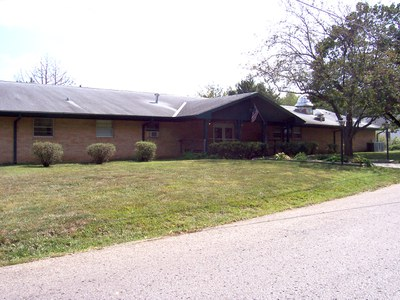 Image of a brick facility building and grass lawn. Three shrubs are in front of the building. The building has a door and windows and appears as one story.