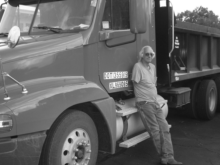 Grayscale image of a man leaning against a large truck. He is wearing a t-shirt and jeans. He does not have a right arm. He has shoulder-length grey hair and is wearing dark sunglasses.