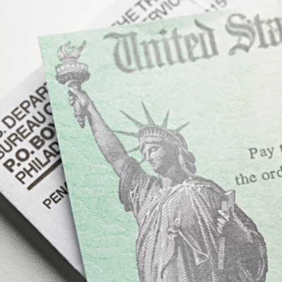 This is a close up image of a U.S. Treasury check on top of an envelope. A grayscale image of the Statue of Liberty is on the green check.