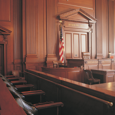 """Image of a courtroom. The walls have wood paneling and behind the judges chair states """"In God We Trust."""" The witness stand on the left is visible and has an American flag behind it. One row of seats is shown in the image."""