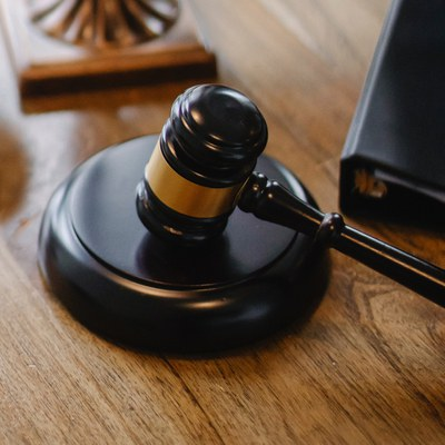 This is an image of a wood gavel. The gavel is resting on a circular, raised piece of dark wood. It is on top of a table. The gavel itself has a gold strip around the middle. Part of a black binder is shown next to the gavel.