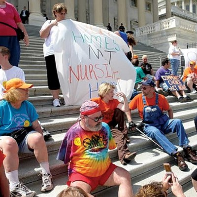 Image of a disability rights protest at the U.S. capitol building. Around 15 people are sitting on the Capitol steps. Two people are holding up a sheet that has something unreadable written on it.  Other people are holding posters in the background.
