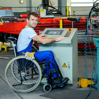 A white adult man using a wheelchair is sitting in front of an operating board in a mechanical shop. He is wearing blue overalls and a white t-shirt. He has gloves sitting on his lap.