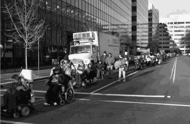 A line of people move through a city street with tall buildings on the side. Two people using power chairs lead the march. Behind them are many more people - some walking, some using power chairs, and some using manual wheelchairs.