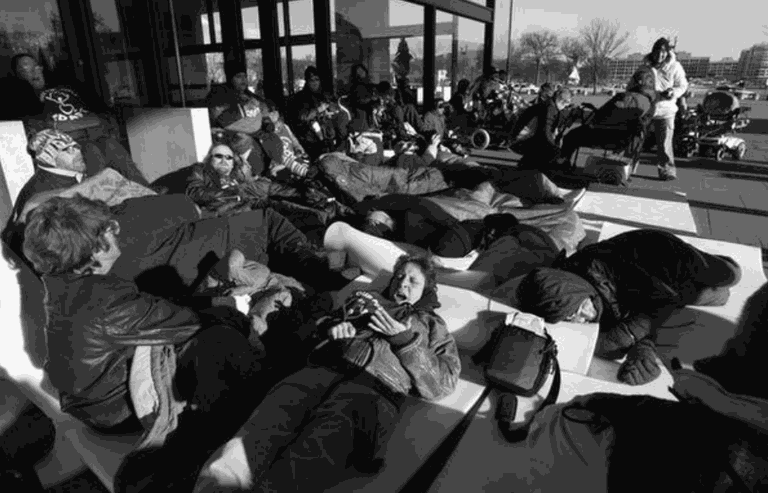 Black and white image of around 20 people laying outside of a city building.