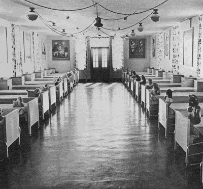 Black and white image of a large room with beds lining both walls. The room is decorated with posters. A stuffed animal is on each bed.