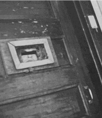 Black and white image of a woman looking out of a small, rectangle opening in a wooden door. There is a black bar over her eyes.