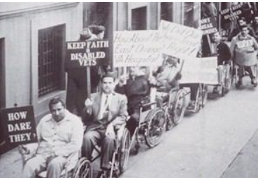 """This is a black and white photograph of about twenty disabled veterans in wheelchairs. The men are waiting in a line on the sidewalk along the wall of an office building. The wall looks like the façadeof a government building, with smooth grey stone and tall, barred windows. The men wear clothes of the 1940s and 1950s: wide lapels, white socks and dark shoes, cardigan sweaters. One man smokes a pipe and is wearing a suit with a wide striped tie and Argyll socks. The men hold signs that say: """"How Dare They?""""; """"Keep Faith in Disabled Vets""""; """"How About the East Orange VA Hospital""""; """"We Did Our Share, Treat Us Right"""": """"PVA""""; """"Don't Break Promises""""."""