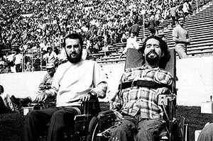 Black and white image of two men in wheelchairs. Both men have dark hair with beards and mustaches. There is a crowd behind them.