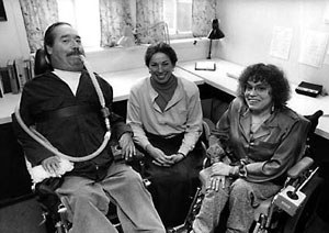 Black and white image of three people in an indoor room. On the left is Ed Roberts. He is using a wheelchair and a breathing device that goes from his mouth to behind his back. He has dark hair and a mustache. He is wearing khaki pants and a dark button up shirt. In the middle is a woman with her hair pulled back. She is wearing a button down shirt and a long skirt. On the right is Judy Huemann. She is wearing a button down shirt and dress pants. She has short, curly hair and is using a wheelchair.