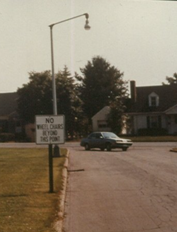 """This is a faded color photograph showing a flat suburban neighborhood street. It is quiet and deserted. There is no sidewalk but a slightly worn grassy footpath edges the side of the street. A flat area of close cut grass extends out from the curb along the street. There is a street light on a high pole. In the background rises a two-story brick building and two white houses with big trees in the front yards. TV aerials are visible on rooftops in the distance. A car is just rounding the corner at the far end of the street and headed this way, perhaps into a parking lot or down another street. There is a white metal sign with black letters placed at the curb that reads: """"No Wheel Chairs Beyond this Point."""""""