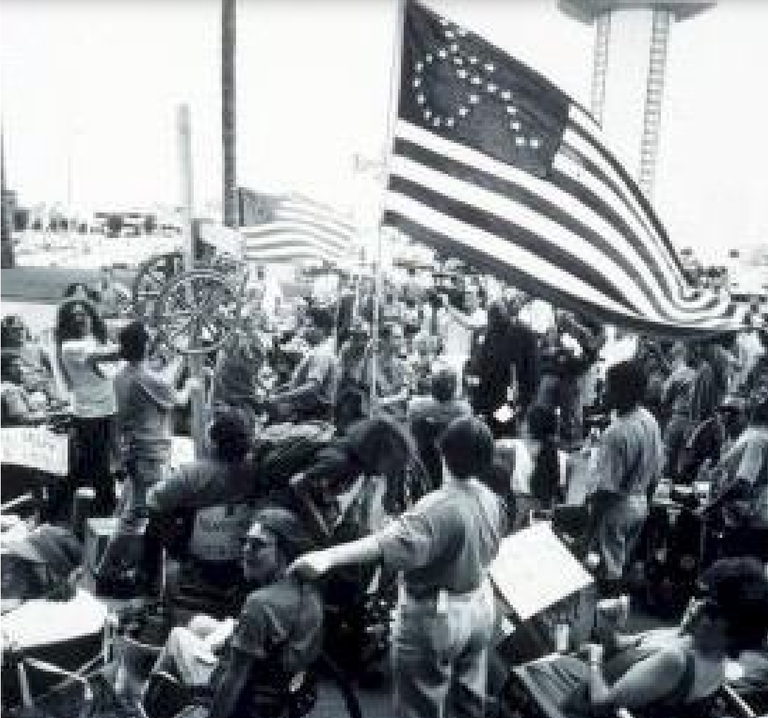 Black and white image of a crowd of people. A large flag is waving. It is designed similarly to the U.S. American flag, with stripes and a navy blue rectangle in the upper right corner. Instead of white stars in rows, stars form the shape of a person in a wheelchair.
