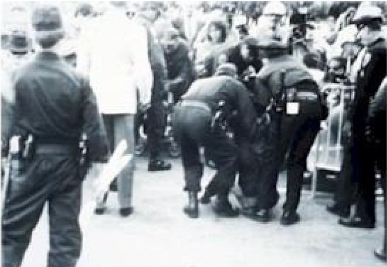 Black and white photo. Two police officers are arresting someone who is not visible in the image. They are leaning toward the ground.