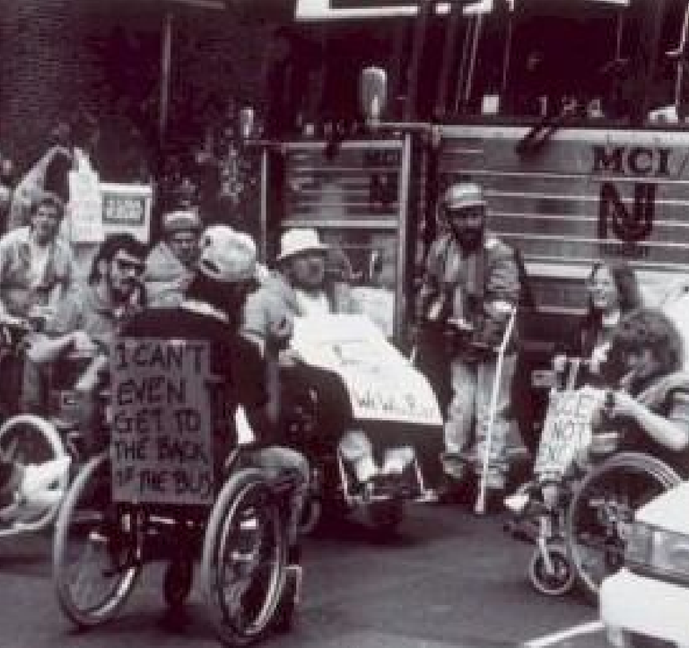 """Black and white image of people in wheelchairs and other mobility assisting devices in a parking lot. Someone is in a wheelchair closest to the camera with a sign on the back of the chair that reads """"I CAN'T EVEN GET TO THE BACK OF THE BUS."""" Other people have signs that are unreadable in the image."""