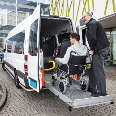 A white adult man is pushing another white adult man's wheelchair up a metal ramp into a white van. The van is outside of a building on a driveway path.