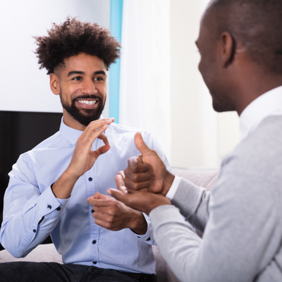 Photo of two Black men facing each other in sitting position. The man on the right has a beard and mustache and is wearing a blue button-up shirt and black slacks. He is signing in ASL toward the other man. The second man's face is not visible to the camera but he is wearing a white collared button down with a grey sweater. He is also signing in ASL toward the other man.
