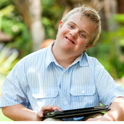 A white adult man with a developmental disability smiles at the camera. He is blonde and is wearing a light blue, button-up, short sleeve shirt with white pinstripes. He is holding a tablet and is touching the screen with his right index finger. The background is trees and plants but is blurred.