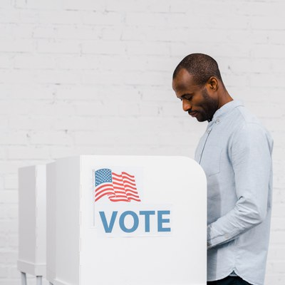 """A Black adult man is standing and looking down over a polling station. The polling station has a sticker that says """"VOTE"""" with an American flag. The man has short hair and a stubble. He is wearing a button down, light blue shirt."""